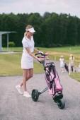 Selektivní fokus ženské golfové hráče v čepici a bílé polo s golf zařízení na golfovém hřišti