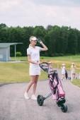 Fotografie Selektivní fokus ženské golfové hráče v čepici a bílé polo s golf zařízení na golfovém hřišti