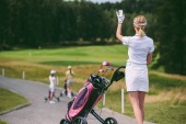 selective focus of female golf player in cap and white polo with golf gear greeting friends at golf course