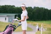Selektivní fokus atraktivní ženské golfové hráče v čepici a bílé polo s golf zařízení na golfovém hřišti