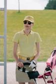 Ritratto del giocatore di golf femminile in protezione ed occhiali da sole in piedi vicino a campi da golf presso il campo da golf