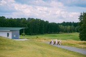 female golfers with golf gear walking at golf course on summer day