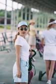 Selektivní fokus ženy v sluneční brýle s golfové vybavení při pohledu kamery na golfovém hřišti