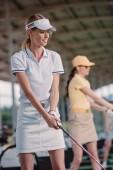 Selektivní fokus usmívající se žena hraje golf s přítelem na golfovém hřišti