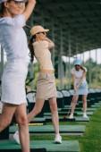 Selektivní fokus žen v caps hrát golf na golfovém hřišti