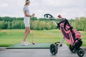 side view of woman in polo and cap with golf club standing at golf course