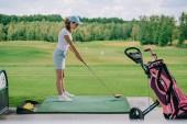boční pohled na ženy v polo a čepici hrát golf na golfovém hřišti