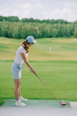 Fotografie side view of woman in polo and cap playing golf at golf course