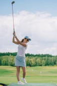 boční pohled na ženy v polo, sluneční brýle a čepici hrát golf na golfovém hřišti