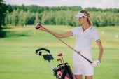 Fotografie portrait of female golf player in cap with golf gear at golf course