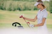 Fotografia fuoco selettivo del giocatore di golf femminile in protezione con attrezzatura da golf presso Golf sorridente