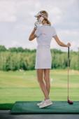Fotografie boční pohled na ženské golfové hráče v polo a čepici s golfového klubu v ruce mluví na smartphone na golfovém hřišti