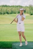 Fotografie ženské golfové hráče v polo a čepici s golfového klubu v ruce mluví na smartphone na golfovém hřišti