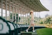 donna in cappuccio giallo e polo giocando a golf presso il campo da golf