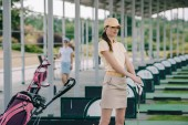 selective focus of female golfer in polo and cap with golf club looking at camera at golf course