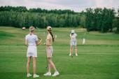 Selektivní fokus žen v caps s golfové vybavení při pohledu na přítele hrát golf na golfovém hřišti