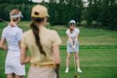 selektiven Fokus der Frauen in der Kappen mit Blick auf Freund Golfen am Golfplatz Golfausrüstung