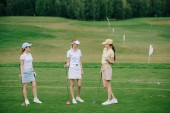 Fotografie women in caps with golf equipment having conversation at golf course