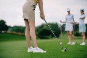 Fotografie partial view of woman playing golf with friends near by at golf course