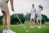 Selektiver Fokus lächelnder Frauen in Mützen mit Golfausrüstung, die ihre Freundin beim Golfspielen auf dem Golfplatz beobachten