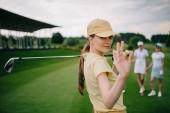 Fotografie Selektivní fokus ženské golfové hráče s ok znamení ukazující na golfovém hřišti golfového klubu