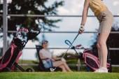 Fotografie částečný pohled ženské golfové hráče hrát golf zatímco přítel odpočívá za na golfovém hřišti