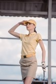 portrét zamyšlený ženské golfové hráče v čepici s golfového klubu koukal