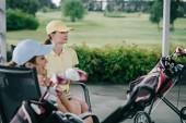 boční pohled na ženy v caps odpočívá po golfové hry na golfovém hřišti
