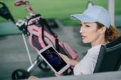 Seitenansicht einer nachdenklichen Golfspielerin mit Tablet in der Hand auf dem Golfplatz