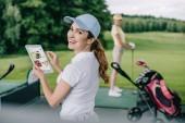 Selektiver Fokus einer lächelnden Frau mit Tablet mit ebay-Logo und einem Freund, der auf dem Golfplatz hinterherspielt