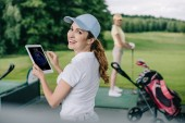 selective focus of smiling woman with tablet and friend playing golf behind at golf course