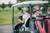 zadní pohled na ženské golfisté CAPS na koni golfový vozík s vybavením na golfovém hřišti