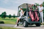 Fotografie usmívající se ženské golfové hráče na golfový vozík připravuje pro hru na golfovém hřišti