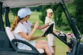Selektivní fokus ženské golfistů v caps v golf vozík pozdrav přítele s golfové vybavení na golfovém hřišti
