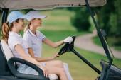 boční pohled na ženské golfisté CAPS na koni golfový vozík na golfovém hřišti