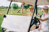 smiling female golfers in caps riding golf cart at golf course