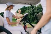 usmíval se ženské golfové hráče pozdrav přítele v golfovém vozíku na golfovém hřišti