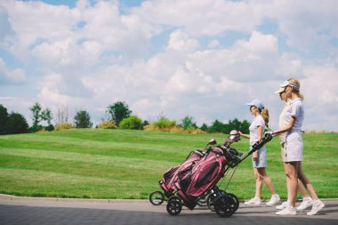 side view of female golfers with golf equipment walking at golf course