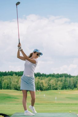 side view of woman in polo, sunglasses and cap playing golf at golf course