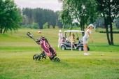 Fotografia messa a fuoco selettiva della donna con il golf club giocando a golf e gli amici che riposa al carrello di golf sul prato verde