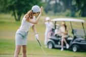 Fotografia messa a fuoco selettiva della donna con il golf club saluta gli amici al carrello di golf sul prato verde