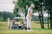 Selektivní fokus ženy s golfového klubu hrát golf a přátelé odpočívá na golfový vozík na zeleném trávníku