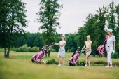 smiling women in caps with golf equipment walking on golf course