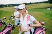 usmívající se ženy v caps s golfové vybavení na hřiště