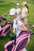 Fotografie Selektivní fokus žen v caps s golfové vybavení na hřiště