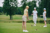 Fotografie smiling woman in cap playing golf while friends standing near by at golf course