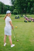 Fotografie side view of smiling female golf player in cap with golf club standing at golf course