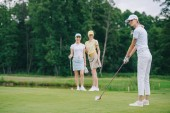 Fotografie Selektivní fokus ženy v čepici, hrát golf, zatímco přátelé stál nedaleko na golfovém hřišti