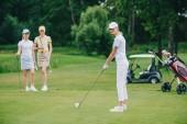 Fotografia messa a fuoco selettiva della donna in protezione di giocare a golf mentre gli amici in attesa vicino al campo da golf