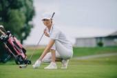 Fotografie ženské golfové hráče v čepici a golfové rukavice uvedení míč na zeleném trávníku na golfovém hřišti